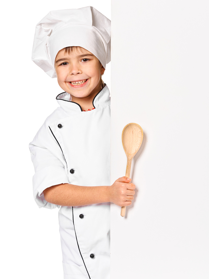 girl chef with large spoon peeking behind empty board. Isolated on white